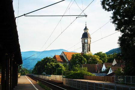 Small railway station, a tower with clock, houses with tile roofs and mountains at the background, Nagymaros, Hungary.
