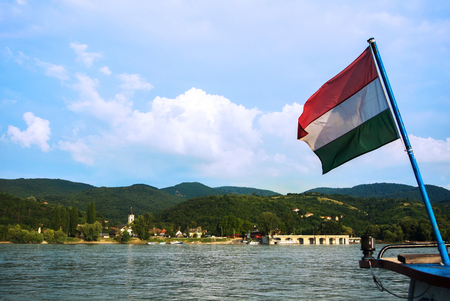 A view to a church at Visegrad, a small town at Hungary near Budapest from a ship at Danube, and a hungarian flag at the foreground. Stock Photo