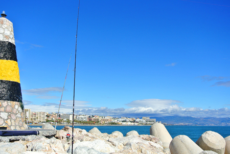 A view to Mediterranean sea, a lighthouse with breakwaters, fishing rods of locals and Torremolinos at the background from a pier at Benalmadena port Puerto Marina, Andalusia, Spain. Stock Photo