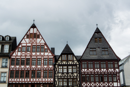roemerberg: FRANKFURT, GERMANY - JUNE 4, 2017: Traditional german decorated houses at the Frankfurt Old town square on cloudy rainy summer day.