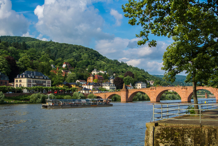 HEIDELBERG, GERMANY - JUNE 4, 2017: River Nickar embankment, touristic boat, Old bridge and a hill at the background on sunny summer evening.