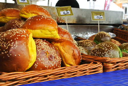 am: FRANKFURT, GERMANY - JUNE 6, 2017: A set of fresh burger buns of different color with sesame seeds in the baskets prepared for cooking at the street farm market, Frankfurt am Main, Germany.