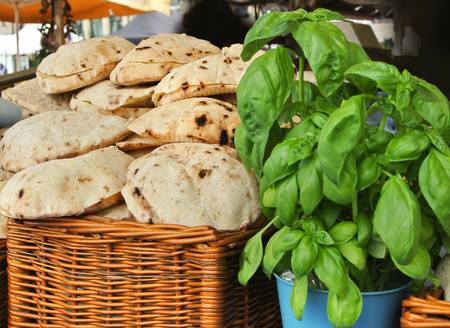 am: A basket with fresh baked homemade pitas and a basil plant at the street farm market, Frankfurt am Main, Germany.
