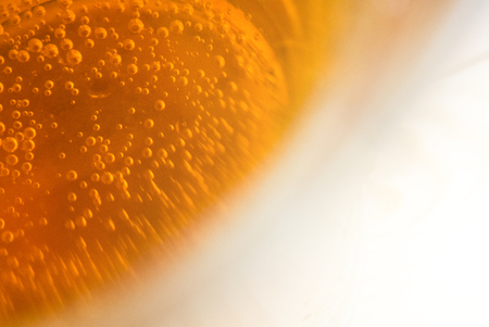 selected: Close-up background of a beer glass standing on a bright light wooden table with plenty of air bubbles, selected focus.