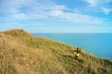 Beachy Head cliff, the highest at Seven Sister country park and graves of suicides who jumped down and blue seascape of English channel at tha background, Eastblurne, East Sussex, England, UK.