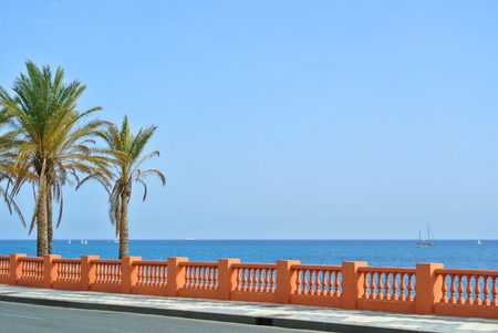 A view to Mediterranean sea from a waterfront promenade of Benalmadena beach and a road with palms at the forefround, Malaga province, Andalusia, Spain. Stock Photo