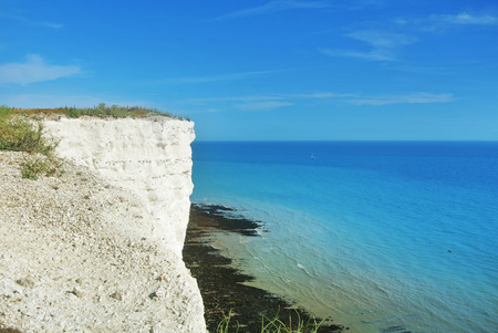 Aerial view to blue turquoise water of English channel and a little white sailboat at the background and white chalk stones of cliffs, Seven Sisters country park, Eastblurne, East Sussex, England, UK. Stock Photo