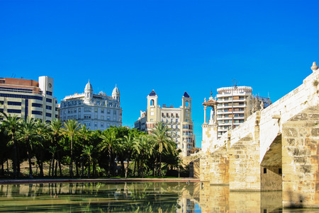 ebro: A historic stone bridge Puente Del Mar and a pond near it with residential apartment buildings and a row of palms in the center of Valencia, Spain on sunny day.