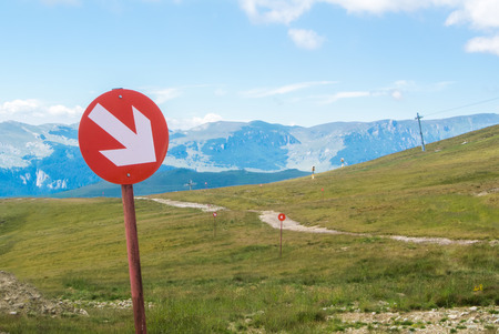 ski walking: Ski trails at Carpatian mountains on autumn day, red signs with arrows, Bucegi natural park, Romania.