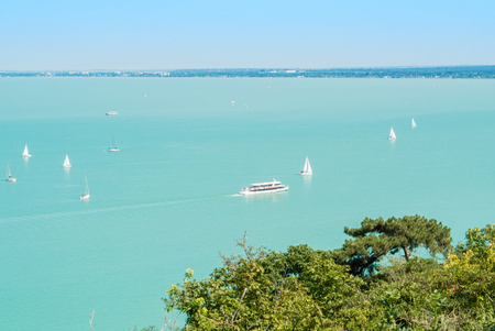 A view from above to Balaton lake from the hill with white yachts and trees at the foreground, Tihany, Hungary.