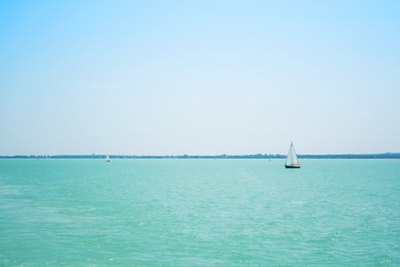 A view from a ship to bright Balaton lake water and coast at the background on sunny summer day, Hungary. Stock Photo