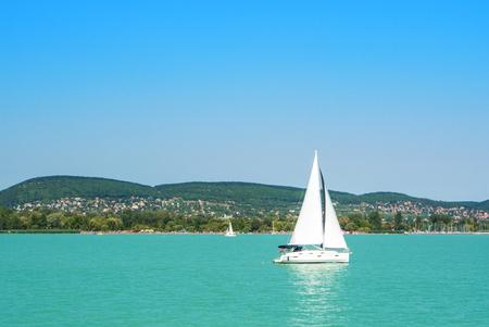 밝은 발라 톤 호수 물과 도시, 숲과 산 하얀 화창한 여름 날, 헝가리에 배경에서 우주선에서보기.