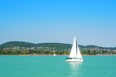 A view from a ship to bright Balaton lake water and a white yacht with a town, forest and mountains at the background on sunny summer day, Hungary. Archivio Fotografico