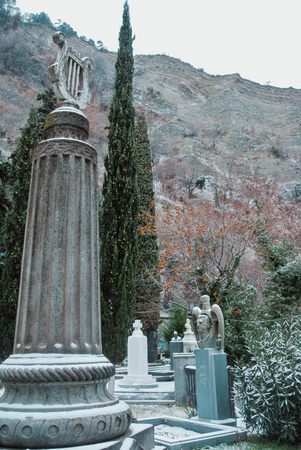 TBILISI, GEORGIA - JANUARY 1, 2016: Georgian cemetery near Mama Daviti church at Mtatsminda, Tbilisi, Georgia. Old monuments covered with the snow and cypress at the background. Editorial