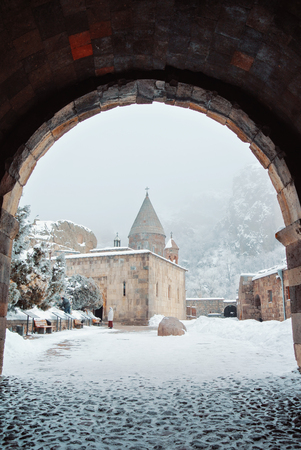 Armenian monastery Geghard, a view through an tuff arch entrance to a church yard, pavement and trees covered with snow with mountains and fog at the background.