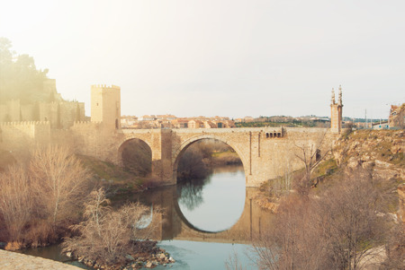 An arch Alcantara Bridge over the Tagus River and its reflection in water on winter evening day, Toledo.