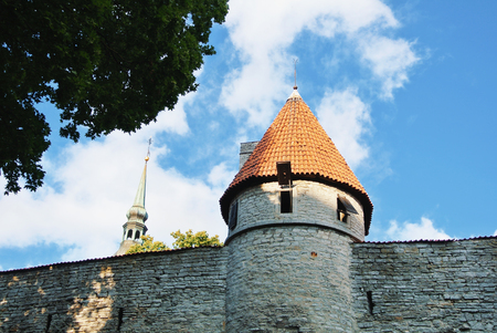 A view to Tallin Old Town walls with a tower and steeple of Saint Nicholas Church at the background, Estonia.