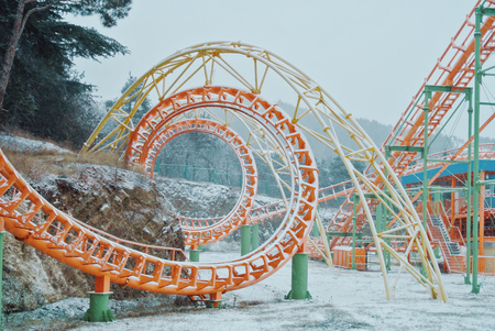 Abandoned amusement theme park covered with falling snow on a cold cloudy winter day. Orange, green and yellow constructions of roller coaster slides, trees and a fence at the background.