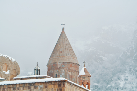 A dome of armenian monastery Geghard, trees covered with snow with mountains and fog at the background.