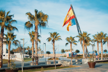 VALENCIA, SPAIN - FEBRUARY 3, 2016: A road to Valencia beach, palms and two big spanish and valencian flags. Editorial