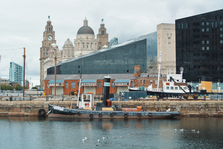 LIVERPOOL, ENGLAND - AUGUST 10, 2013: A view to Liver Building and old vintage fishing ship from the Albert Dock on cloudy day.