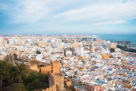 Aerial panoramic view of Almeria old town and sea coast from the castle (Alcazaba of Almeria) over the mountain, Andalusia, Spain. Fortress walls at the foreground.