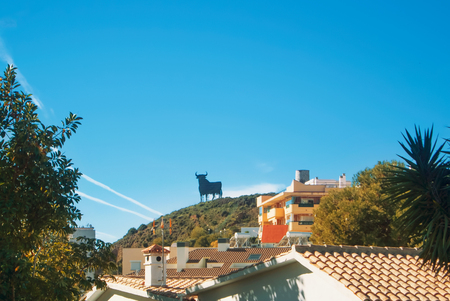 Toro Osborne, iconic symbol of Spain, silhouette of black bull on the hill over Fuengirola town, houses with tile roofs at the foreground.