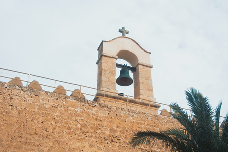 Close up of a bell over the wall of medieval moorish fortress Alcazaba in Almeria and cloudy sky on the background, Andalusia, Spain. Stock Photo