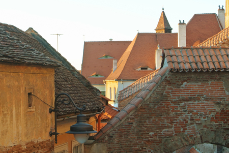 Old traditional romanian vintage orange brown houses with dormers attic windows designed in eyes shape at tile roofs in the evening at city center. Stock Photo