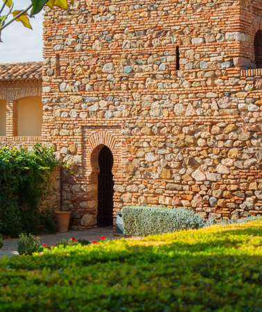 MALAGA, SPAIN - FEBRUARY 16, 2014: A courtyard with old medieval stone brick walls and arch entrance, plants and flowers at the gardens of the famous Palace Fortress of Alcazaba in Malaga, Andalusia. Editorial