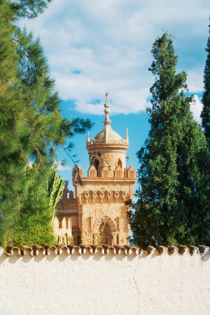 BENALMADENA, SPAIN - FEBRUARY 06, 2015: Close-up view to a tower of Colomares castle in Benalmadena, dedicated to Christopher Columbus, and green trees around. Malaga province, Costa del Sol.