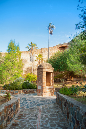 MALAGA, SPAIN - FEBRUARY 16, 2014: A view to old medieval walls, trees, plants, palms and a tower at Gibralfaro Castle of Malaga, Andalusia, Spain, on sunny evening. Editorial