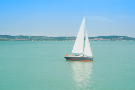 A view from a ship to bright Balaton lake water and a white yacht on sunny summer day, Hungary.