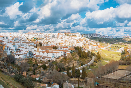Aerial panoramic view of Ronda, tradational white houses with tile roofs on the hill and its surroundings, one of most famous white villages (pueblos blancos) in Malaga province, Andalusia, Spain.