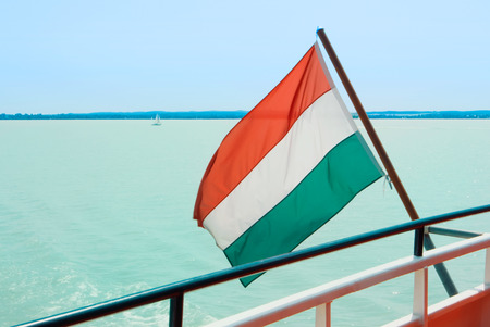 Hungarian flag at the cruise ship with bright light blue water of Balaton lake at the background Hungary.