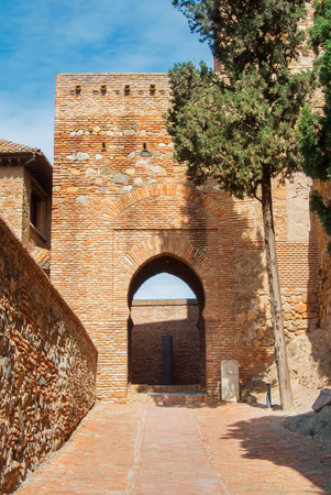 A courtyard with old medieval stone brick walls and arch entrance and plants at the gardens of the famous Palace Fortress of Alcazaba in Malaga, Andalusia, Spain, on sunny day. Editorial