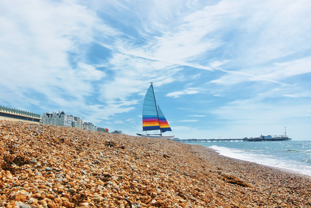 A beautiful yackt vith colorful sail standing near the water waves of English Channel at the beach of Brighton covered with small pebble stones, East Sussex, England, UK.