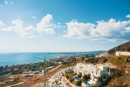 A view from the viewpoint over the hill near The Buddhist Stupa in Benalmadena town to white houses and constructional cranes, Fuengirola and Mediterranean sea at the background.