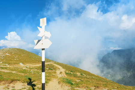 A signpost direction white sign arrow near the tracking path at the peak top of the mountain showing the right hiking direction way route trail and a panoramic view to mountains and clouds of fog.