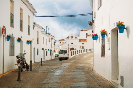MIJAS, SPAIN - FEBRUARY 08, 2015: White narrow streets with whitewashed traditional andalusian houses, blue pots with red geranium at the walls at little touristic town village Mijas, Andalusia, Spain 新闻类图片