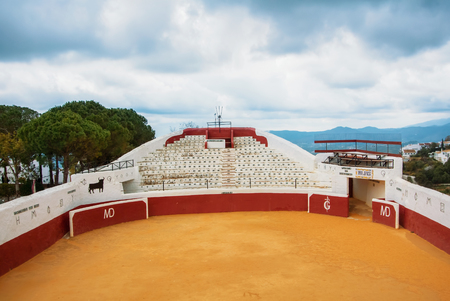 MIJAS, SPAIN - FEBRUARY 08, 2015: Old traditional bullring in Mijas with empty seats on cloudy day, Costa del Sol, Malaga province.