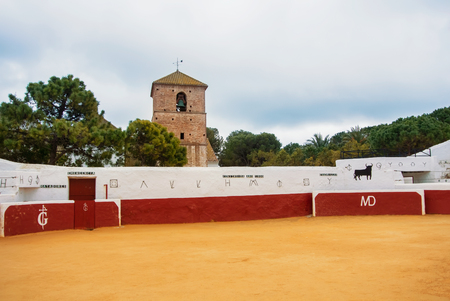 MIJAS, SPAIN - FEBRUARY 08, 2015: Old traditional decorated bullring in Mijas with empty seats and a church bell tower at the background on cloudy day, Costa del Sol, Malaga province. Sajtókép