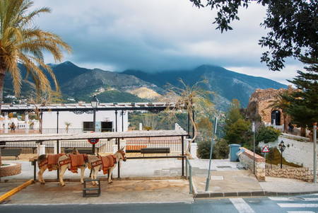 MIJAS, SPAIN - FEBRUARY 08, 2015: Donkey taxi of white village town Mijas and aerial panoramic view to mountains and clouds, Malaga province, Costa del Sol, Andalusia, Spain.