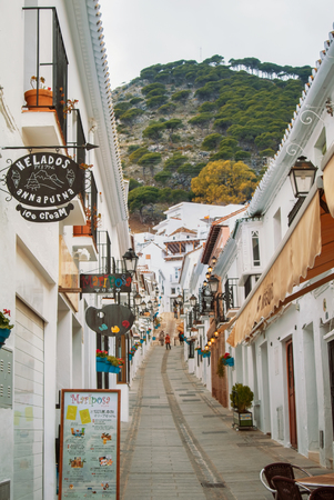 MIJAS, SPAIN - FEBRUARY 08, 2015: White narrow streets with whitewashed traditional andalusian houses, cafes and shops at little touristic town village Mijas, Andalusia, Spain, on cloudy day.