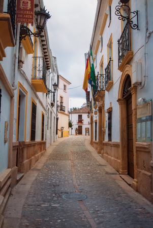 RONDA, SPAIN - FEBRUARY 03, 2014: Narrow cobble stone paved street with traditional andalusian white houses and flags in pueblo blanco Ronda, cloudy sky at the background. 新闻类图片