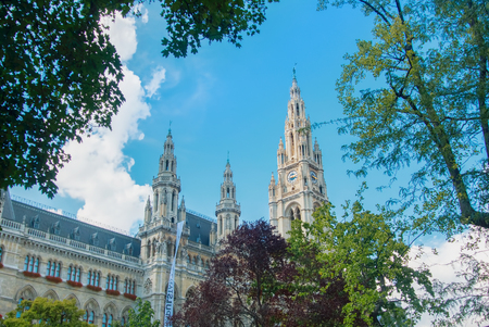 VIENNA, AUSTRIA - JULY 29, 2016: City hall (Rathaus) ant high trees in the park on sunny summer day at Vienna, Austria.