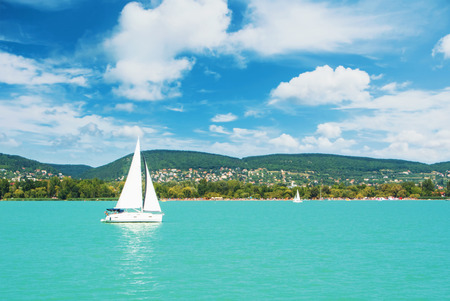 Panoramic view of lake river blue transparent water, a white sport modern luxury yacht sail boat floating and a green shore with forest, hills, villages and beach. Holiday by the water and sail race.