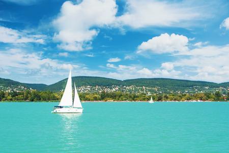 호수 강 푸른 투명 한 물, 하얀 스포츠의 파노라마보기 현대 럭셔리 요트 항해 보트 부동 및 숲, 언덕, 마을과 해변 녹색 해안. 물과 항해 레이스에 의해