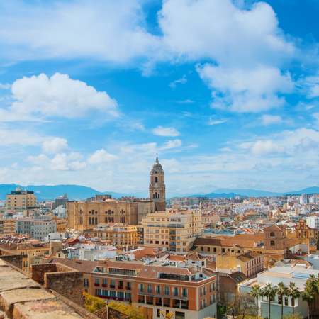 Aerial panoramic top view over the roofs to a tower of Malaga Cathedral from the walls and towers of Castillo Gibralfaro (Castle of Gibralfaro) on sunny cloudy day, Andalusia, Spain. Travel in Spain.