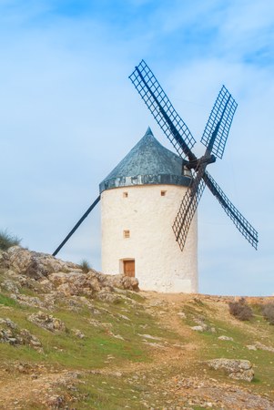 Old white traditional windmill on the hill near Consuegra (Castilla La Mancha, Spain), a symbol of region and journeys of Don Quixote (Alonso Quijano) on cloudy day. Stock Photo